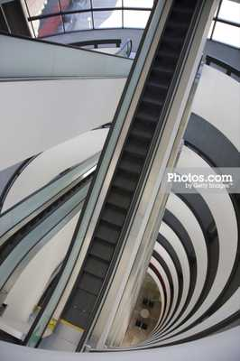 Looking down at grey escalator and white walls - Photos.com by Getty Images